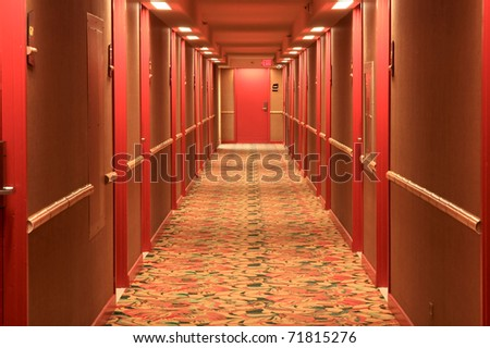 Hotel hallway with red doors and carpet.