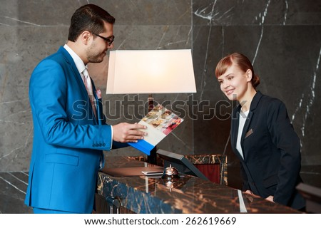 Hotel information available. Good-looking businessman holding an information holder copyspace asks receptionist about services provided by the hotel  - stock photo