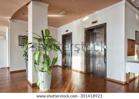 Hotel lobby with passenger elevator - stock photo
