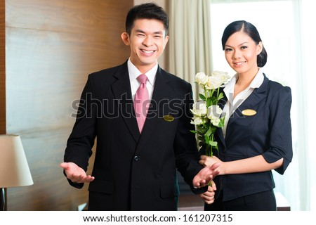 Hotel Manager or director and supervisor welcome arriving VIP guests with roses on arrival in luxury or grand hotel - stock photo