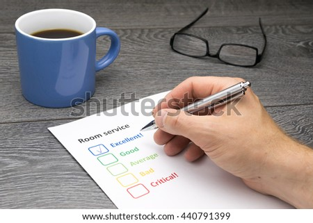 Hotel offering excellent room service. Customer filling out survey form while having a coffee - stock photo