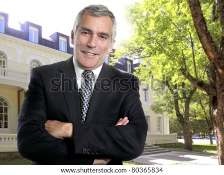hotel or real estate senior businessman with suit posing on building facade [Photo Illustration] - stock photo