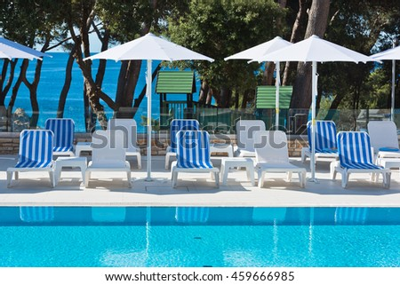 Hotel Poolside Chairs with Sea view. Summer shot