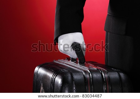 Hotel porter carrying suitcase, close up, side view - stock photo