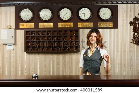 Hotel reception. Female receptionist at reception gives card to a guest. Modern hotel reception counter desk with bell. Woman receptionist at desk. Travel, hospitality, hotel booking concept.  - stock photo