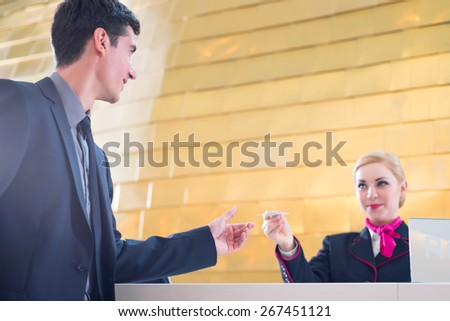 Hotel receptionist check in man giving key card - stock photo