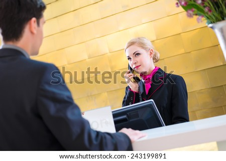 Hotel receptionist telephoning with guest for reservation or information  - stock photo