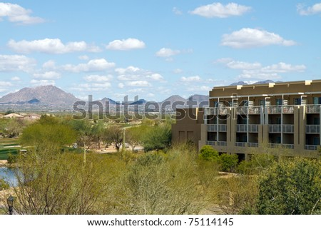 Hotel resort in the Arizona desert desert with a blue sky and mountains in the background; with copy space for text - stock photo