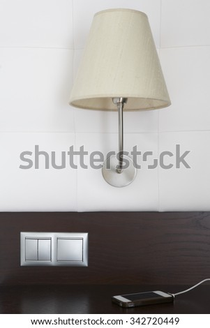 Hotel room interior detail with lamp, switches and smartphone. Vertical - stock photo