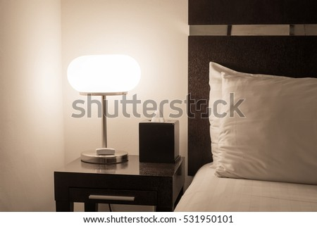 hotel room interior with illuminated bed light on wooden table