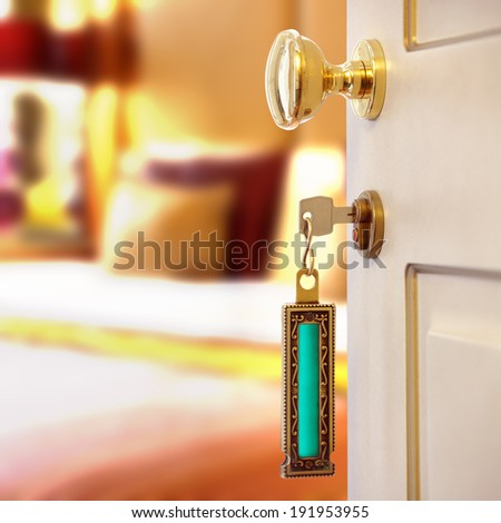 Hotel room or apartment doorway with key and keyring key fob in open door and bedroom in background - stock photo