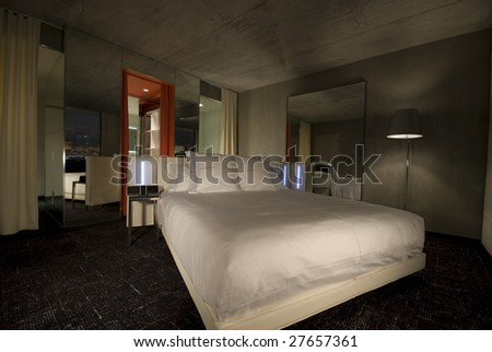 Hotel room with a bed in the middle. - stock photo
