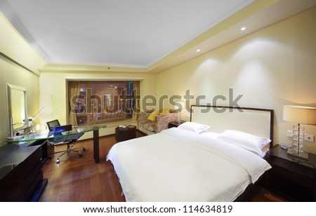 Hotel room with bed, mirror, notebook - stock photo