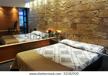 Hotel room with stone textured walls - stock photo