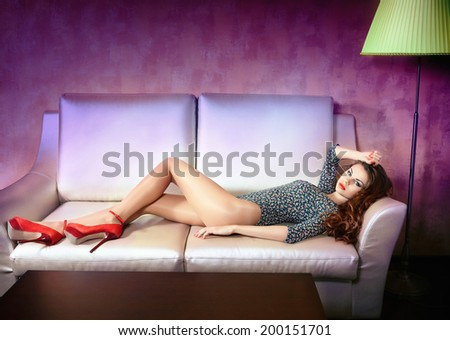 Hotel room. Woman in red shoes on the sofa - stock photo