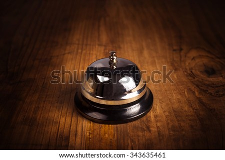Hotel service call bell on wooden reception front desk, retro toned image. - stock photo