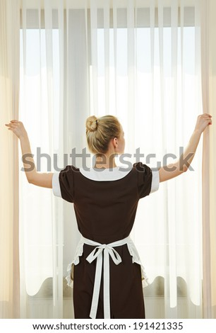 Hotel service. female housekeeping chambermaid worker with opening curtains of window in room - stock photo