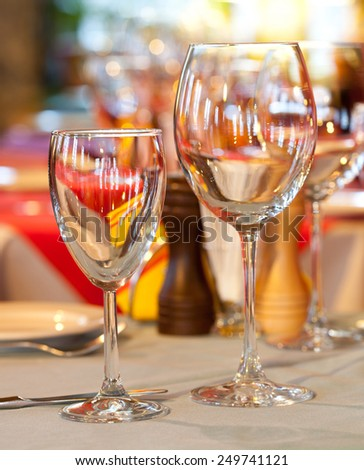 Hotel service: table in a restaurant with tablecloth, red napkins, wine glasses and cutlery. (soft focus - on the small glass) - stock photo
