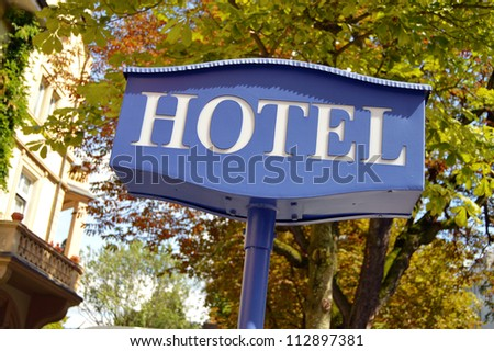 Hotel sign - Hotel signboard with building and trees in the background - stock photo