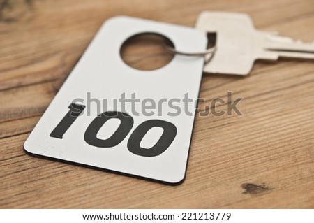 Hotel suite key with room number 100 on wood table