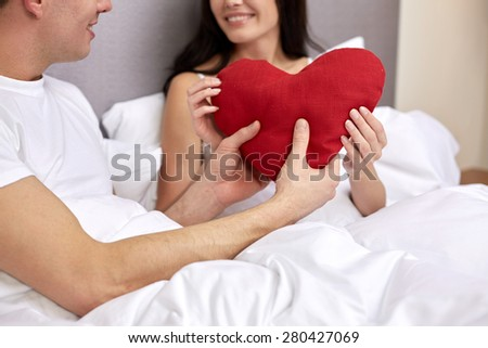 hotel, travel, relationships, holidays and happiness concept - close up of smiling couple in bed with red heart-shaped pillow at hotel or home - stock photo