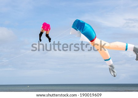 HOULGATE, FRANCE - APRIL 27, 2014: Kites of woman leg shape flying over the sea. Houlgate is a coastal town in Lower Normandy, France