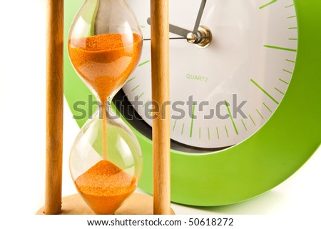 Hour glass and green clock on white - stock photo