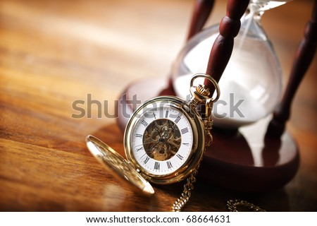 Hour glass or sand timer with vintage pocket watch, symbols of time with copy space - stock photo