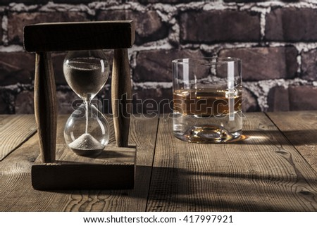 Hourglass and alcohol on brown wood table - stock photo