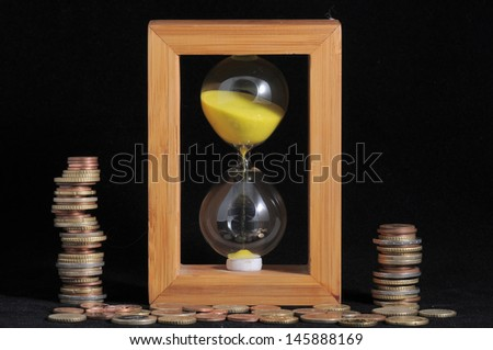Hourglass and Money - Time is Money - stock photo