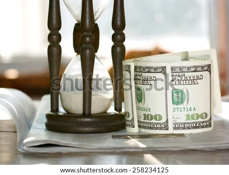 Hourglass and one hundred dollar bills - stock photo