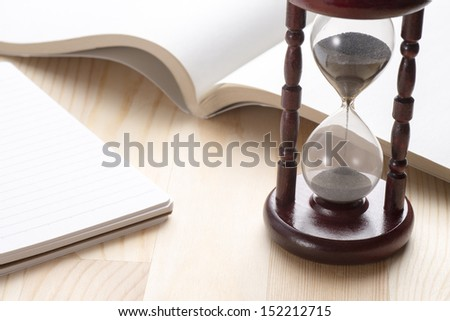 hourglass and open book on wooden table - stock photo