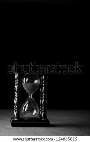 hourglass clock on black background - stock photo