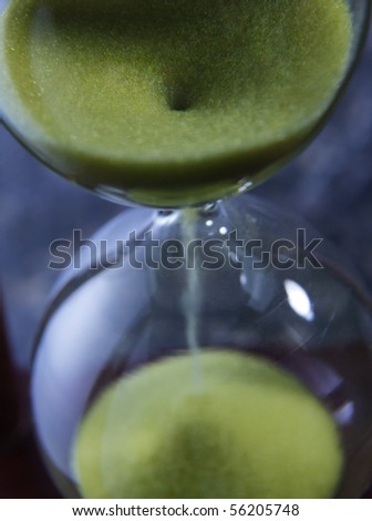 Hourglass - Grains of sand falling down - stock photo