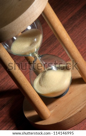 Hourglass - Grains of sand falling down - selective focus - stock photo