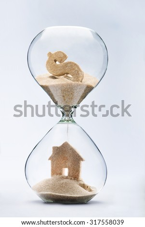 Hourglass house mortgage concept.House made out of falling sand from dollar sign flowing through hourglass - stock photo