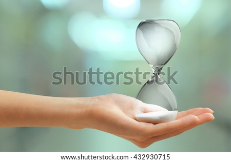Hourglass in female hand on blurred background - stock photo