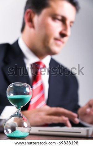 Hourglass in focus and businessman working, deadline concept - stock photo