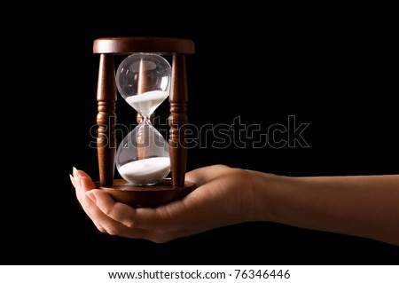 Hourglass in hands on a black - stock photo