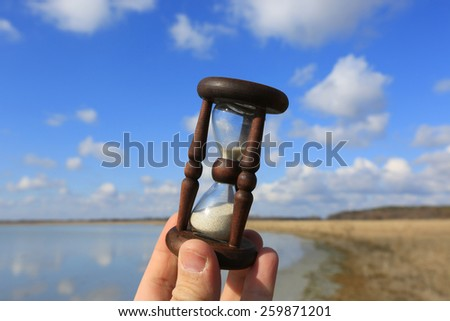 Hourglass in man hand on sky background - stock photo