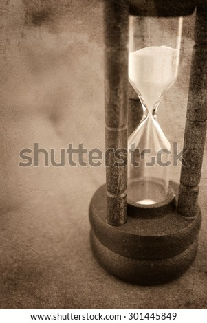 hourglass in vintage style on mulberry paper texture