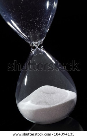 Hourglass isolated on black showing time has run out - stock photo