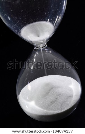 Hourglass isolated on black showing time is running out - stock photo