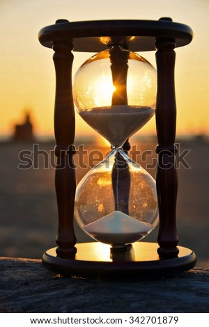 hourglass on a beach log with silhouette of Michigan lighthouse at sunset background - stock photo