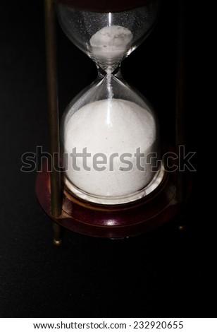 Hourglass on black background - stock photo