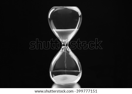 Hourglass on black background - stock photo