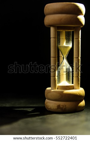 Hourglass on black background,  concept for business deadline, urgency and running out of time