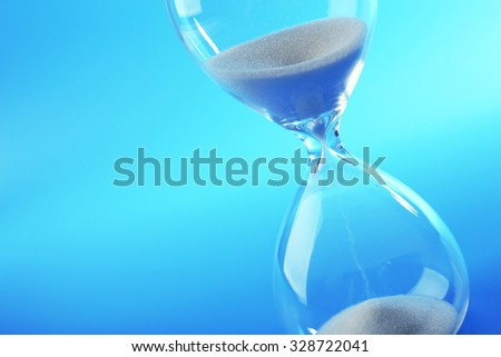 Hourglass on blue background - stock photo