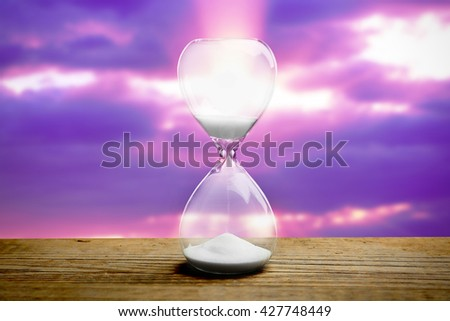 Hourglass on blurred purple sunset background - stock photo