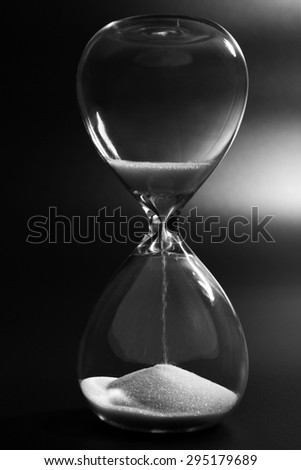 Hourglass on dark background - stock photo
